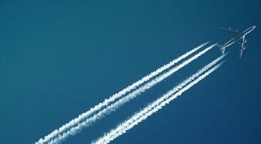 A plane cuts diagonally across a deep blue sky, leaving contrails behind it