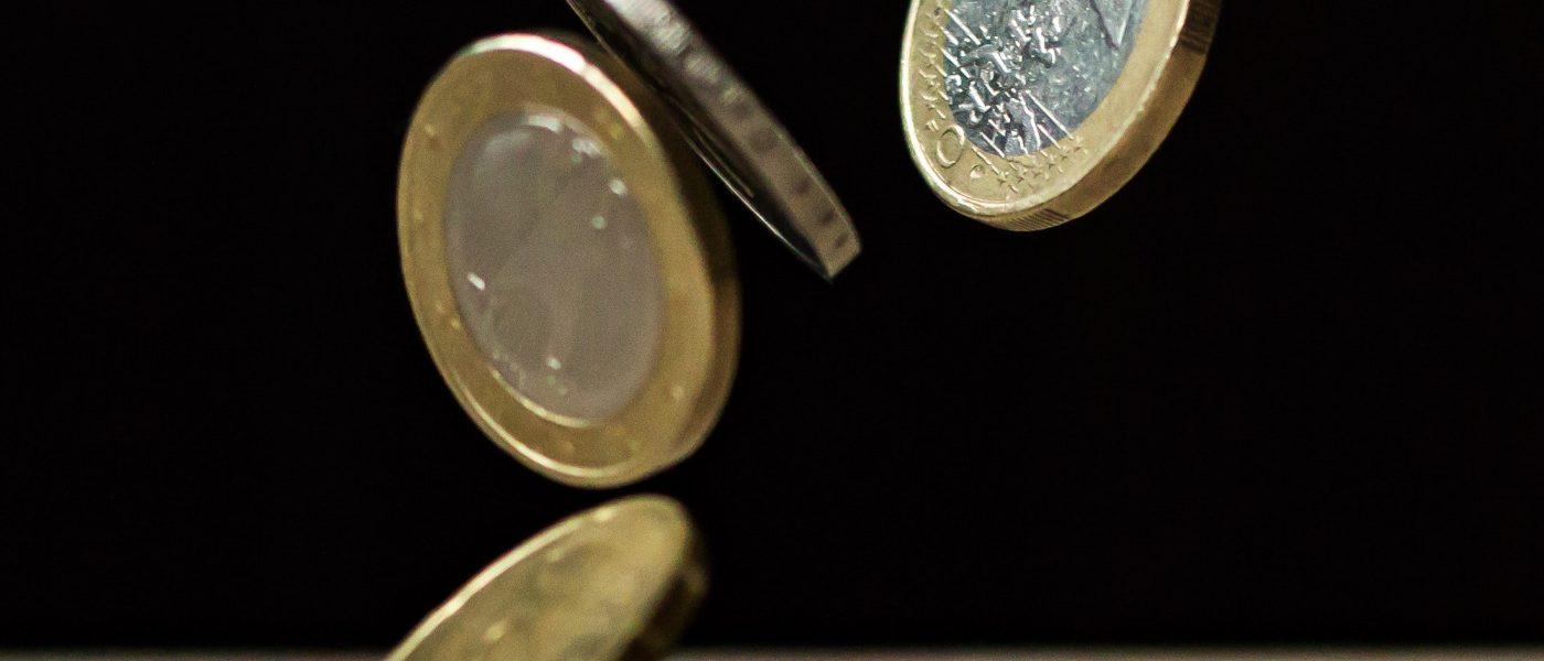 Euro coins bouncing off a table