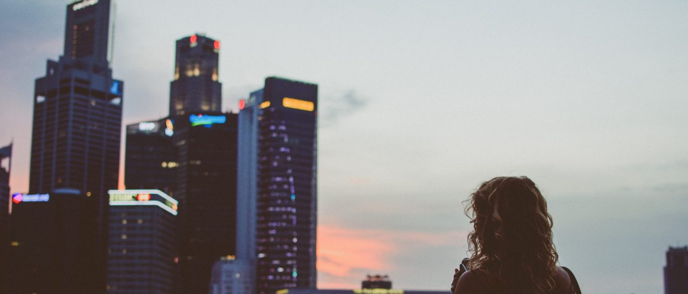 Woman stands facing financial district skyscrapers