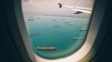 View of port and cargo ships from airplane window